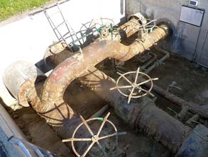 Corroded pipework in the access chamber of a district heating facility